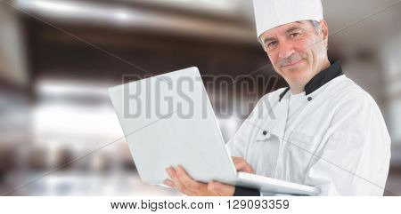 Composite image of friendly chef holding a laptop against a blurred background