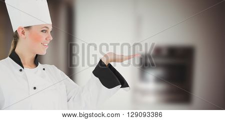 Portrait of a woman chef against image of kitchen equipment