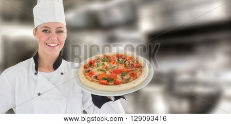 Portrait of a woman chef holding a pizza against work surface and kitchen equipment