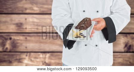 Close up on a chef holding a chocolate cake against wooden planks background