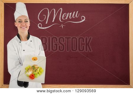 Composite image of woman chef smiling and holding a meal against a blackboard