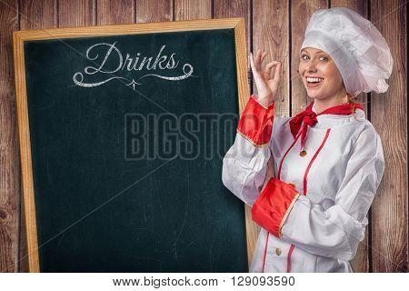 Pretty chef standing with arms crossed against wooden planks background