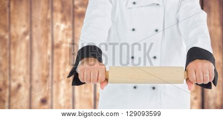 Close up on a chef holding a rolling pin against wooden planks background