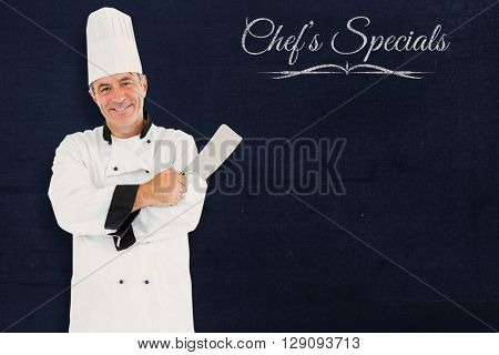 Composite image of friendly chef holding a knife against a blackboard