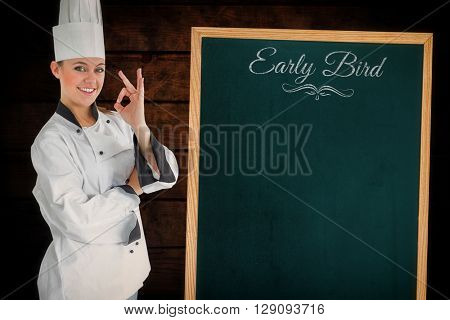 Composite image of satisfying woman chef next to a blackboard