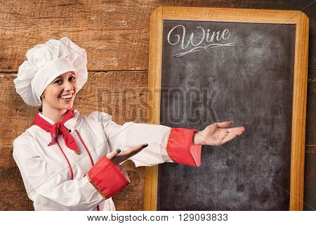 Pretty chef presenting with hands against overhead of wooden planks