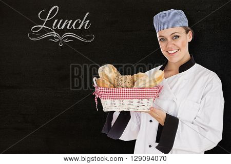 Woman in chef uniform with bread basket against black