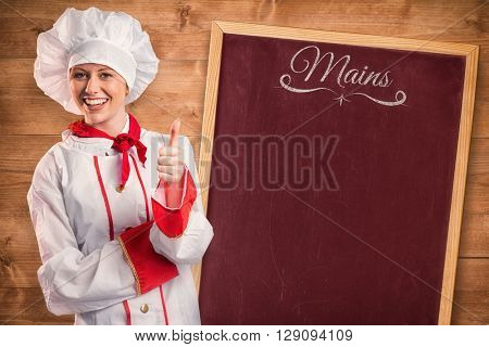 Pretty chef showing thumbs up against bleached wooden planks background