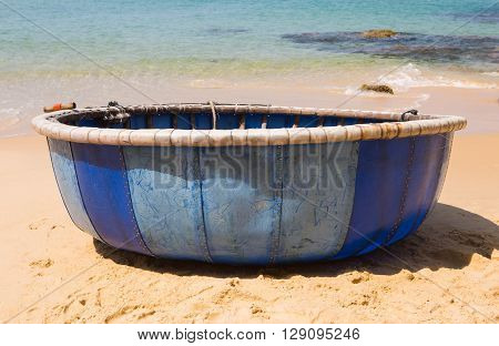Close up of a round plastic fishing boat (named 'Thuyen Thung' in Vietnamese) in the sunlight on sandy beach, central Vietnam.