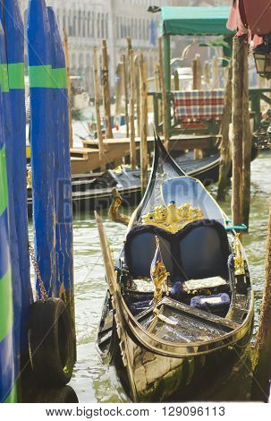 Gondolas moored to wooden posts in Venice. Italy.