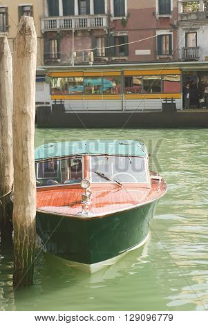Timber boats moored to wooden posts in Venice, Italy.