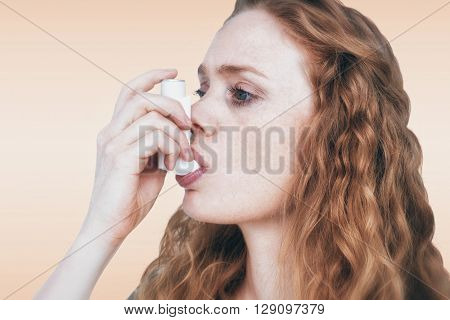Close-up of woman using the asthma inhaler against orange background