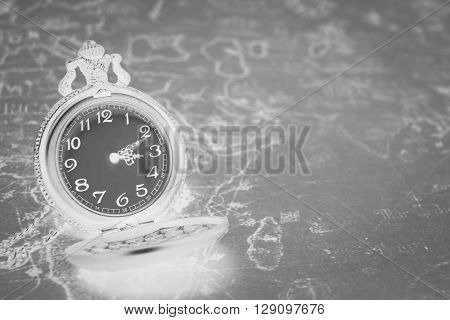 Close up vintage antique pocket watch on old map backgroundblack and white.