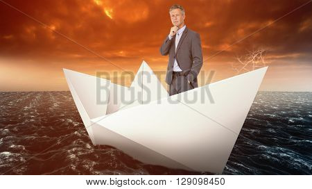 Full length portrait of businessman with hand on chin against paper boat floating on the sea