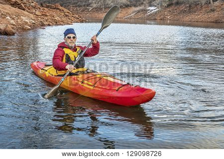 senior male is paddling colorful river kayak on a calm lake  - recreation concept
