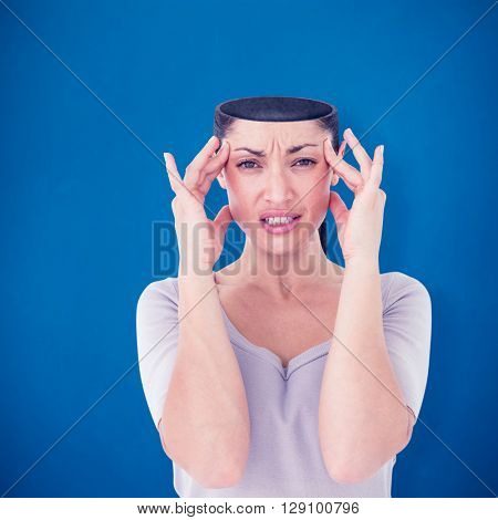 Brunette suffering from migraine against blue background
