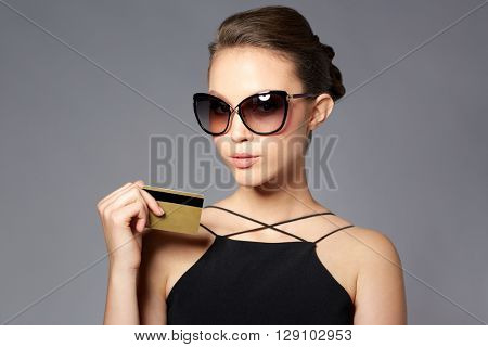 shopping, finances, fashion, people and luxury concept - beautiful young woman in elegant black sunglasses with credit card over gray background