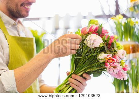 people, business, sale and floristry concept - close up of happy smiling florist man making bunch at flower shop
