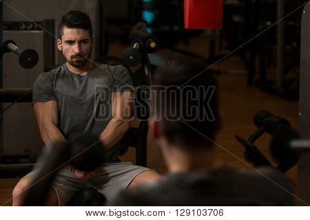 Bodybuilder Showing His Muscles And Posing In Gym