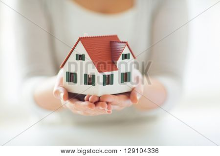 architecture, building, construction, real estate and property concept - close up of hands holding house or home model