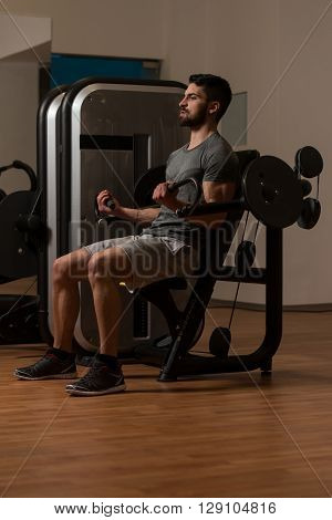 Young Bodybuilder Exercising Biceps On Machine
