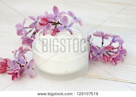 Jar of white facial cream, fresh flowers. Sweet floral aroma skincare.