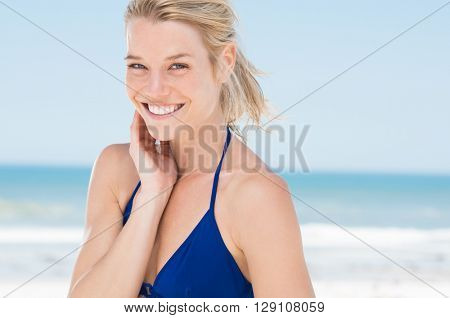 Portrait of attractive woman standing at beach. Happy smiling girl looking at camera at seaside. Young blonde woman relaxing at beach.