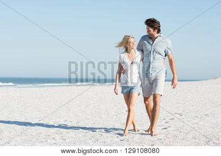 Young couple embracing and walking at the beach on a bright sunny day. Couple in love holding hands and looking each other at the beach. Couple strolling at the beach and smiling, copy space.