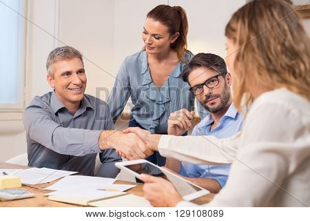 Handshake after a job recruitment meeting. Successful businesspeople shaking hands in front of their colleagues. Mature businessman shaking hands to seal a deal with businesswoman in office.
