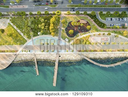 Aerial view of Molos Promenade on the coast of Limassol city in Cyprus. A view of the walk path surrounded by palm trees pools of water grass boardwalk the Mediterranean sea piers rocks and urban skyline.