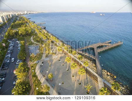 Aerial view of Molos Promenade on the coast of Limassol city in Cyprus. A view of the walk path surrounded by palm trees pools of water grass the Mediterranean sea piers rocks and urban skyline.