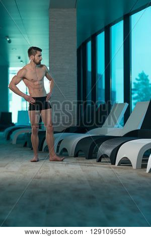 Young Man Flexing Muscles At Sun Lounger