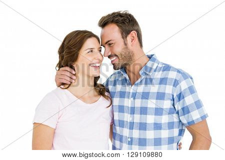 Happy young couple looking at each other and smiling on white background