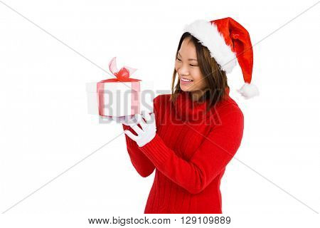 Woman in christmas attire holding gift on white background