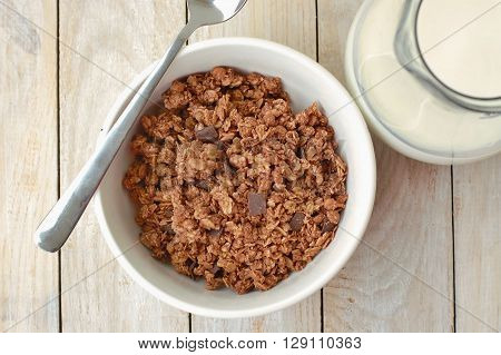 Chocolate Musli With Milk In The Glass Jug On The Wooden Background