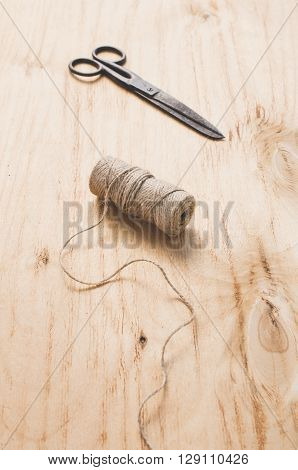 Old scissors and skein jute twine on a wooden background. poster