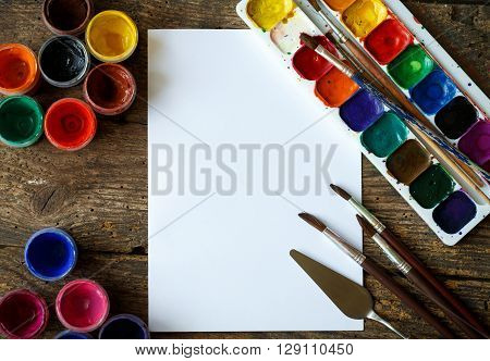 Art of Painting. Painting set: paper brushes paints crayons watercolor acrylic paint on a wooden background