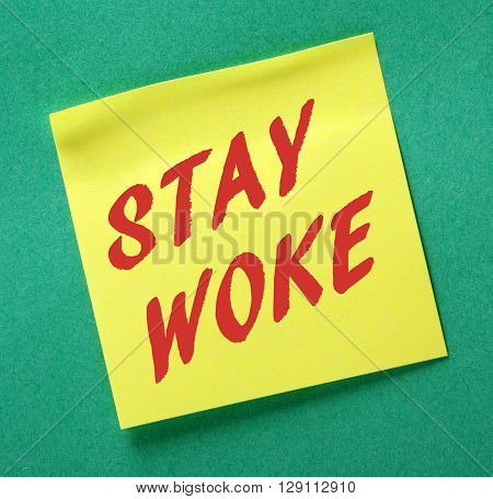 The words Stay Woke in red text on a yellow sticky note as a reminder to remain aware and stay informed about politics and other issues