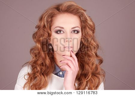 Portrait of young girl 20-24 year old posing in room over grey. Long curly hair. Elegance.