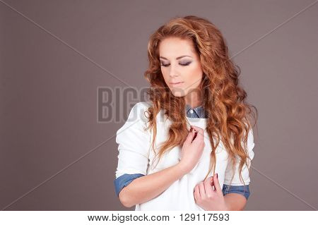Beautiful girl 20-22 year old posing over grey in room. Wearing stylish shirt. Long ginger curly hair. Elegance. Young adult.