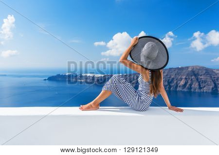 Europe summer vacation travel cruise destination luxury living woman relaxing on outdoor terrace looking at view of Mediterranean Sea and Santorini Oia. Elegant tourist lady in fashion beachwear.