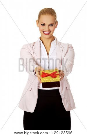 Smiling young business woman holding present box