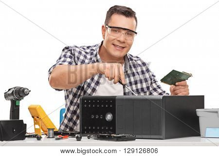 Young PC repairman fixing a broken desktop computer isolated on white background