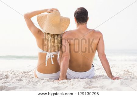 Happy couple sitting on the beach on a sunny day