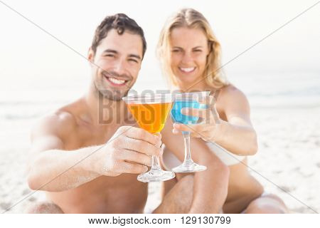 Happy couple sitting and drinking cocktails on the beach