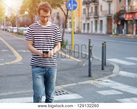 portrait of young adult man crossing inattentively the street distracted by his phone