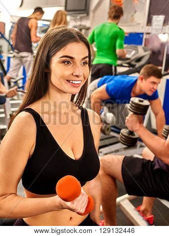 Group of people working with  dumbbells his body at gym. Girl keeps dumbbells on foreground into sport gym.