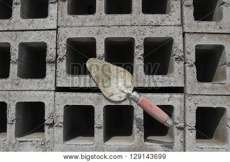 Trowel on cinderblock gray background. against the background of the brickwork is trowel.