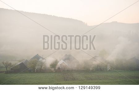 Spring landscape of scenic forest and small village. Smoking the gardens to avoid frost