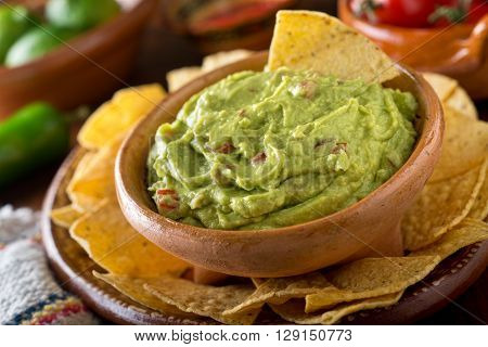 A delicious authentic mexican guacamole dip with avocado lime and tomato.